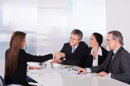 entrevista: Empresarios Mirando a la Mujer agitando la mano Foto de archivo