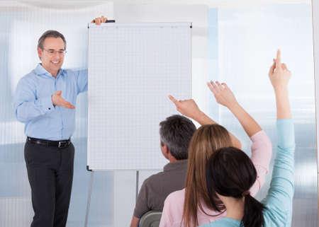 classroom training: Happy Mature Male Teacher Teaching Student In Classroom Stock Photo