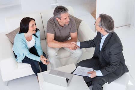 financial agreement: Happy Couple And Mature Consultant Discussing Together Stock Photo