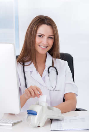Happy Beautiful Female Doctor Inserting Credit Card Into Scanner photo
