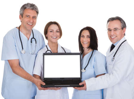 Group Of Happy Doctors Holding Laptop Together photo