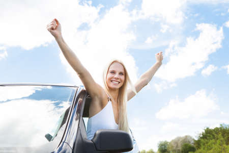 arm extended: Happy Young Woman Raising Hand Out Of Car Window