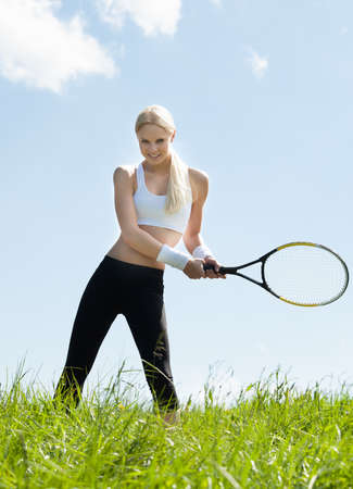 Female Tennis Player Standing In Field Holding Racquet And Ball photo