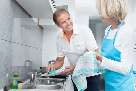 Mature Man Helping His Wife In Household Work photo