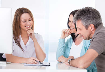 test result: Happy Couple Looking At Results Held By Doctor Stock Photo