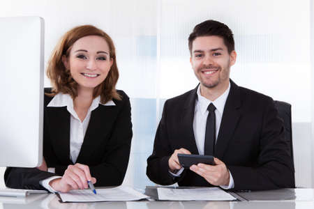 Portrait of two happy business colleagues at office working together photo
