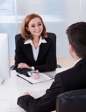 Two businesspeople talking with each other at office photo