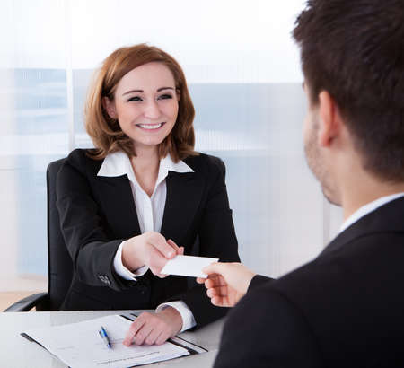 visiting card: Two happy businesspeople exchanging visiting card in office