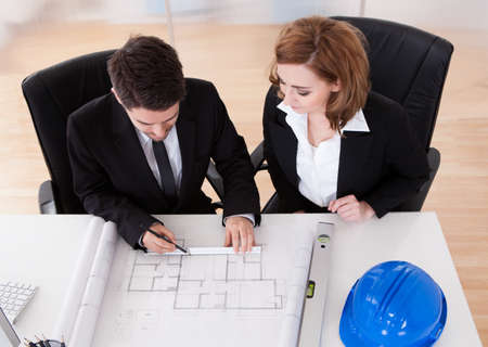 Portrait of two sincere architects working in office photo