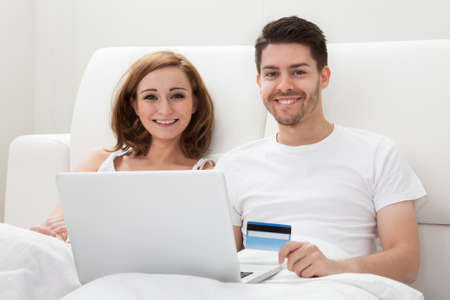 sofa bed: Portrait of young happy couple shopping online