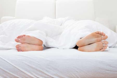 woman bed: Cierre-up de los pies de par que duermen en cama en dormitorio