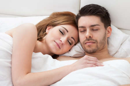 Lovely young couple sleeping on the bed photo