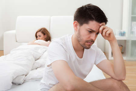 depression: Depressed man sitting on the edge of the bed in bedroom Stock Photo