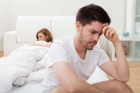 personas discutiendo: Deprimido hombre sentado en el borde de la cama en el dormitorio Foto de archivo