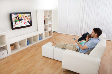 pareja viendo television: Retrato de la joven pareja utilizando el portátil acostado en la cama