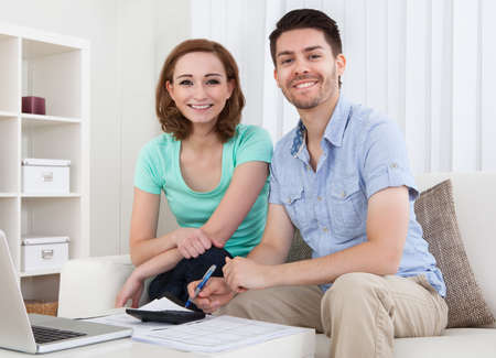 Portrait of young happy couple calculating budget photo