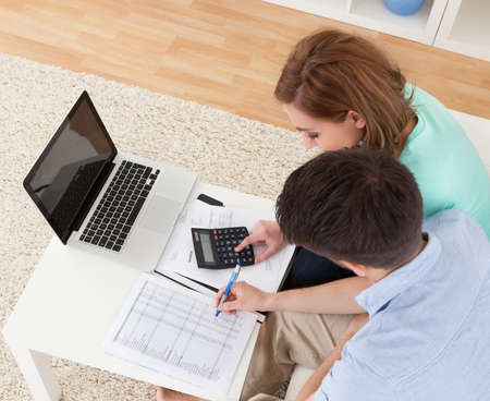 family budget: Portrait of young happy couple calculating budget