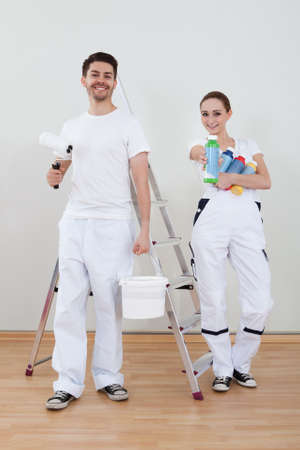 Portrait Of Young Happy Couple Holding Paint Roller photo