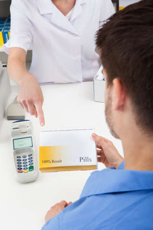 western script: Close-up Of Female Pharmacist Hand Showing Drug In Pharmacy To Client Stock Photo