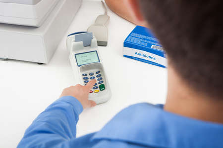 checkout button: Close-up Of Finger Entering The Pin Code In Card Reader Machine