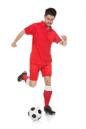 Young  Soccer Player Kicking Ball Over White Background photo