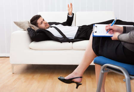 psychiatrist: Business man reclining comfortably on a couch talking to his psychiatrist explaining something