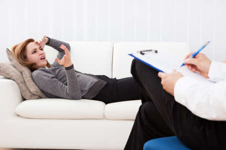 Business woman reclining comfortably on a couch talking to his psychiatrist explaining something photo