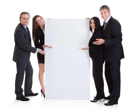 白い背景の上のプラカードを示す幸せなビジネス人々 写真素材