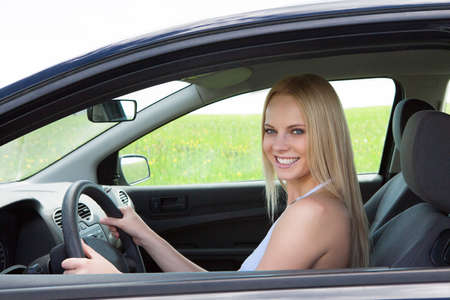 Happy Young Beautiful Blonde Woman Driving Car photo