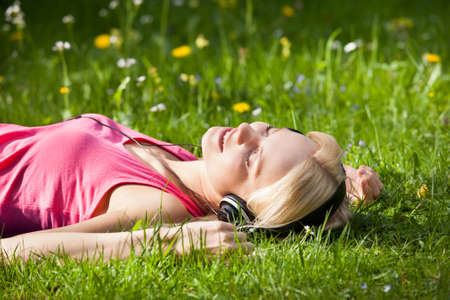 lying on grass: Portrait Of Young Woman Lying On Grass And Listening To Music With Headphones