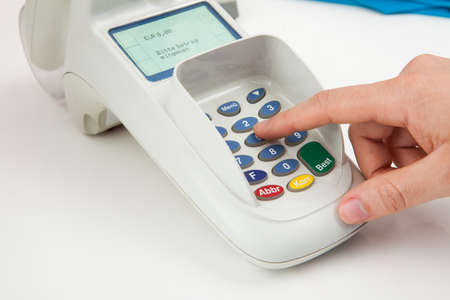 Close-up Of Finger Entering The Pin Code In Card Reader Machine photo