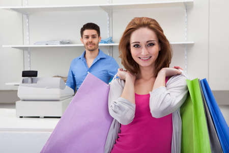 Happy Woman Holding Shopping Bag In Store photo