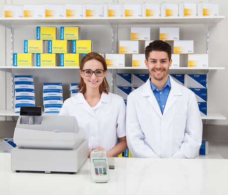 cashier: Portrait Of Two Happy Pharmacist In Pharmacy