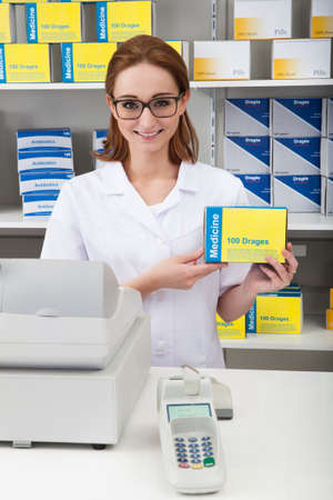 Happy Female Pharmacist Showing Drug In Pharmacy photo