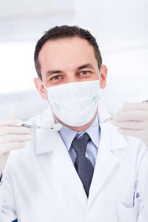 trinchante: Retrato del dentista de sexo masculino Holding Espejo dental y Carver Foto de archivo