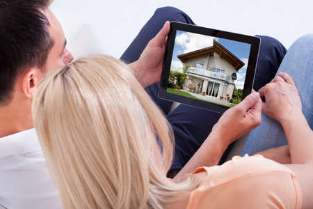 buying online: Couple Looking At House On Digital Tablets Screen Stock Photo