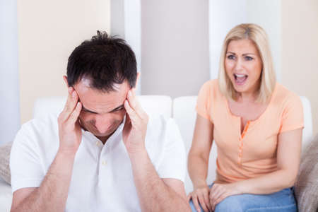 pareja enojada: Retrato de mujer gritando a hombre que consigue dolor de cabeza