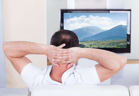 flatscreen: Portrait of man sitting on couch watching television