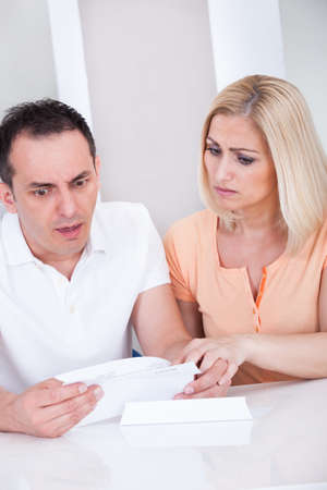 Portrait of shocked couple looking at bill photo