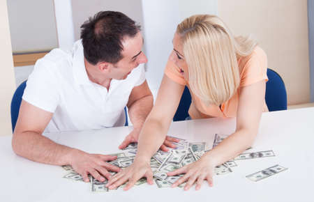 Excited Couple Looking At Each Other Collecting Money On Desk photo