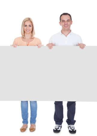 terra arrendada: Casal feliz que prende o cartaz em branco sobre o fundo branco Imagens