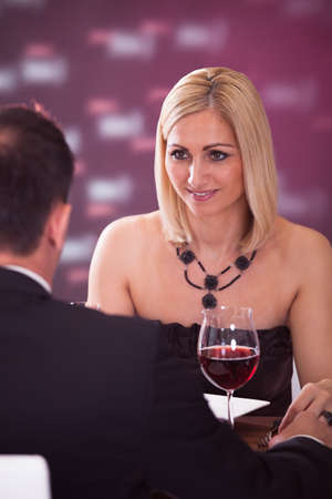 Happy Beautiful Couple Enjoying Meal And Wine In Restaurant photo