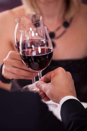 romantic evening with wine: Close-up Of Couples Hand Holding Red Wine And Toasting Glass Stock Photo