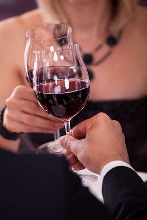 cena romantica: Primo piano della mano della holding delle coppie Vino Rosso E tostatura bicchiere