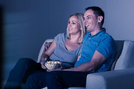 Happy Couple Watching Television And Eating Popcorn At Home photo