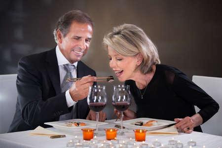 Romantic Mature Couple Having Dinner At Restaurant photo