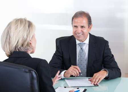 Happy Mature Businessman And Businesswoman In Office photo
