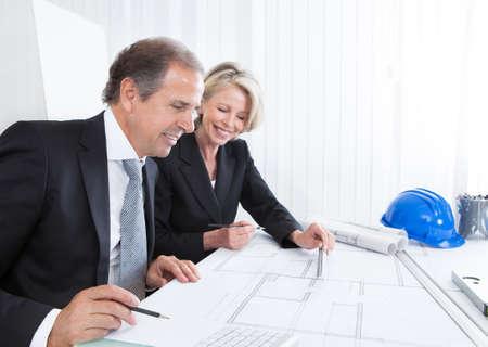 Érett Engineers nézett tervek ül az asztalnál