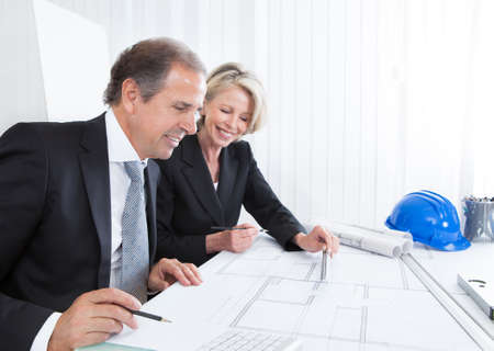 construction company: Mature Engineers Looking At Plans Sitting At A Table Stock Photo