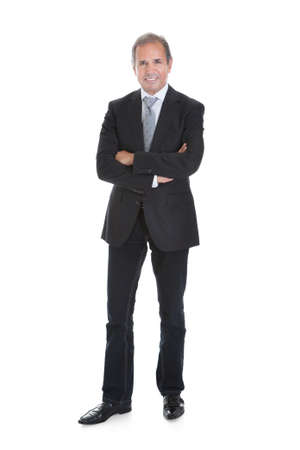person standing: Portrait Of A Well Dressed Businessman Standing With Arms Crossed Stock Photo